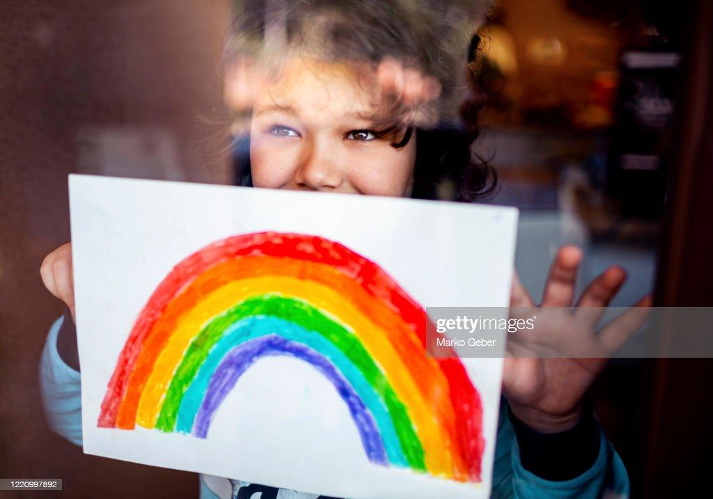 Little boy sticking his rainbow painting on the window : Stock Photo
