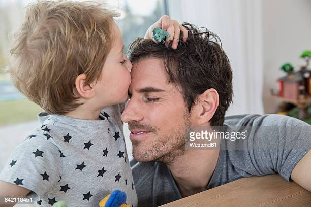 Little boy stroking and kissing his father
