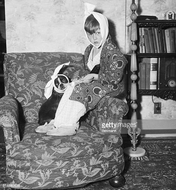 A little boy suffering from the mumps wearing a bandage on his head sits with his little Boston terrier dog Gypsy also wearing a bandage | Location...