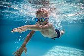 Little boy swimming crawl in pool
