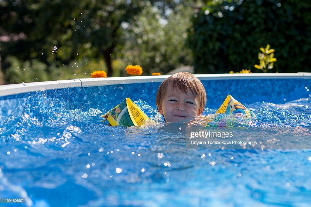 Little boy swimming in a big swimming pool stock photo - How big is an average swimming pool ...
