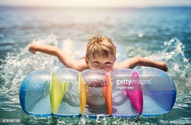 Kleinen Jungen schwimmen auf Luft-Matratze in Wellen des Meeres