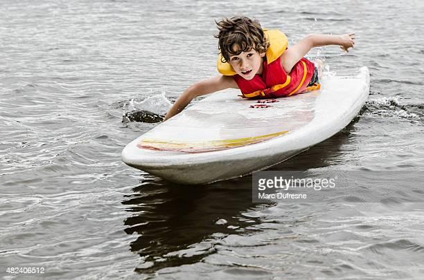 Kleiner Junge Schwimmen surf board