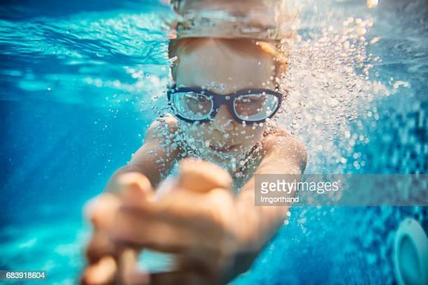 Kleiner Junge unter Wasser schwimmen im Hotelpool