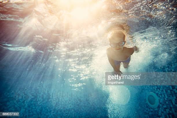 Little boy swimming underwater in hotel pool