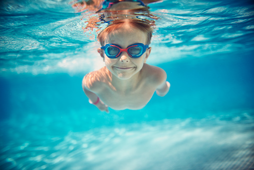 Little boy swimming underwater in pool - gettyimageskorea