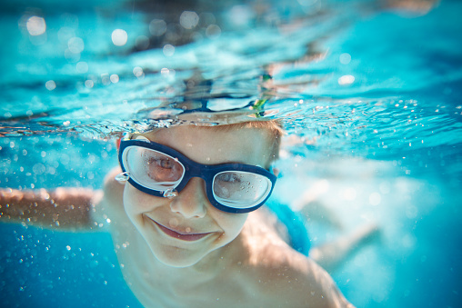 Little boy swimming underwater in pool 621501306