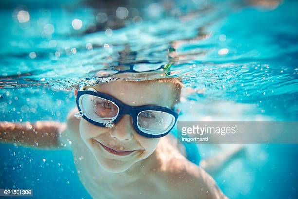 Little boy swimming underwater in pool