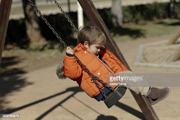 Little boy swinging at the park