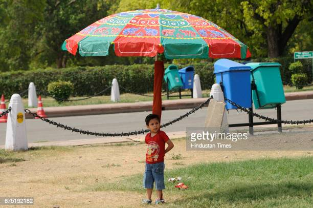 A little boy takes shelter under an umbrella to get respite from the scorching sun on a hot summer day near India Gate on April 30 2017 in New Delhi...