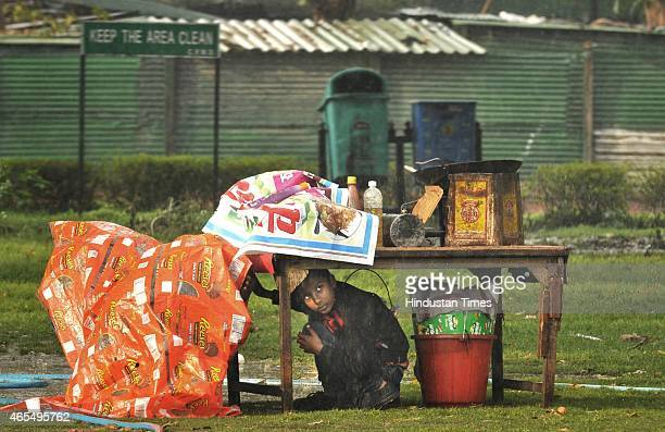 A little boy takes shelter under his stall during heavy rains on March 7 2015 in New Delhi India Heavy rainfall lashed the National Capital Region on...