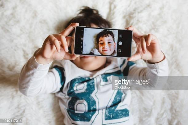 little boy taking a selfie with mobile - click&boo fotografías e imágenes de stock