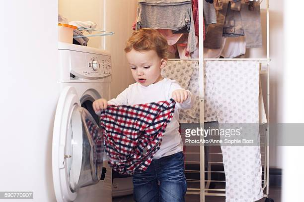 Little boy taking clothes out of dryer