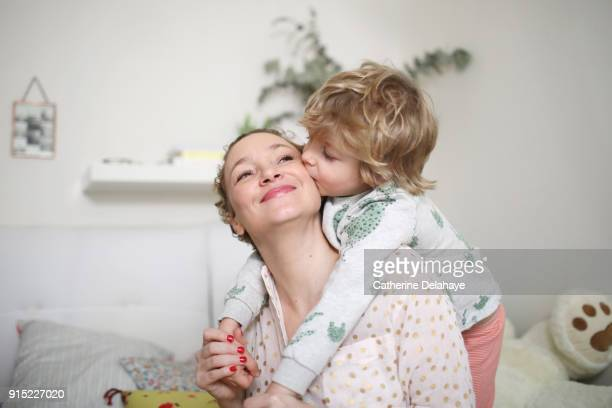 a little boy taking his mum in his arms in the bedroom - offspring stock pictures, royalty-free photos & images