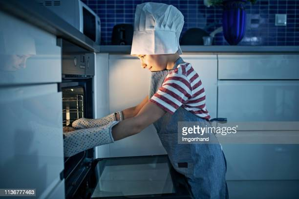 little boy taking out freshly baked cake from oven - imgorthand stock photos and pictures