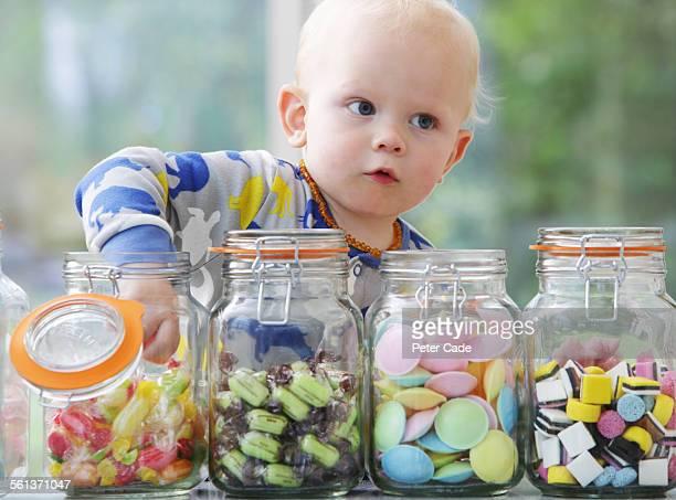little boy taking sweet from sweet pots