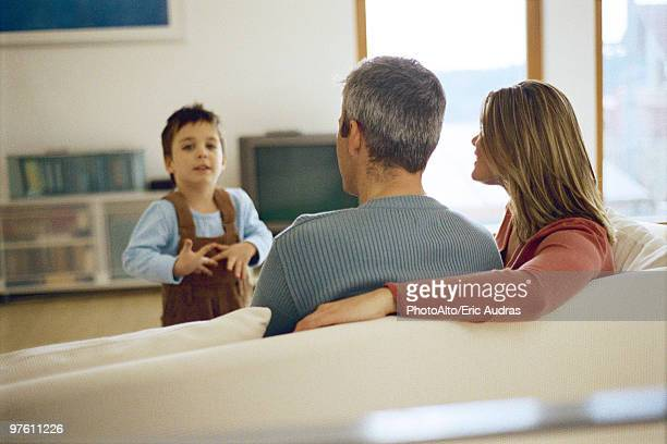 Little boy talking to his parents sitting on the sofa