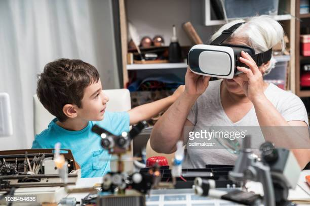 Little Boy Teaching His Grandmother How To Use VR Headset