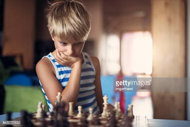 Kleiner Junge denken über seinen Wechsel im Schachspiel