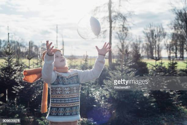 Little boy throwing a snow-filled crystal ball