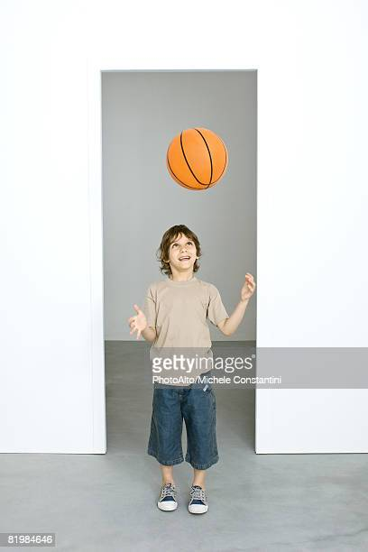 Little boy throwing basketball in the air, looking up, smiling