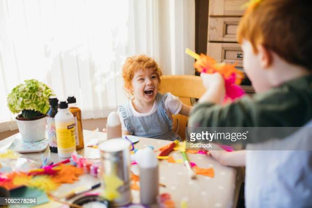 little boy throwing feathers at his sister - 4 girls finger painting stock photos and pictures