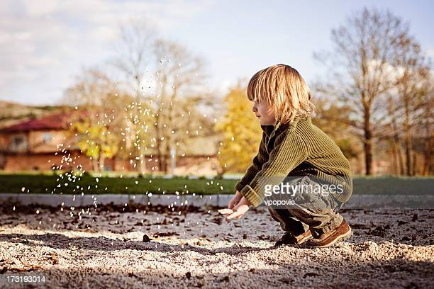 Little boy throwing sand away