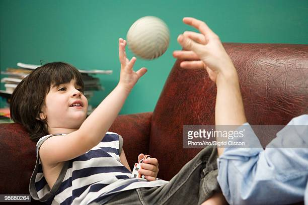 Little boy tossing ball with parent on sofa
