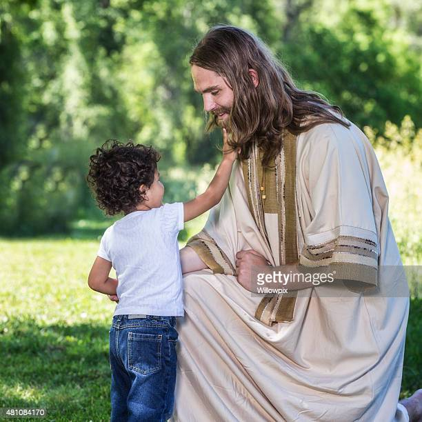 little boy touching beard of kneeling jesus christ - smiling jesus stock pictures, royalty-free photos & images
