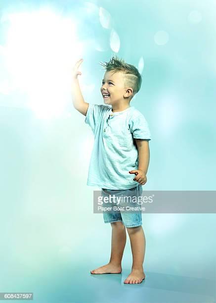 Little boy touching floating ball of light