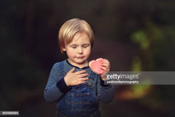 Little boy touching heart while holding a heart shaped cookie