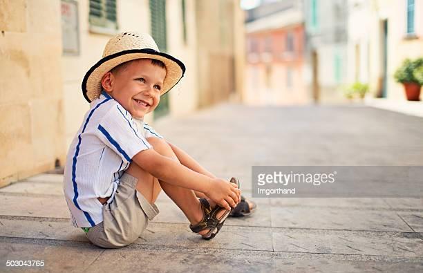 Petit garçon sa chaussure touristiques de fixation dans la ville méditerranéenne.