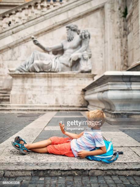 Poco turista niño descansando en la Piazza del Campidoglio, Roma, Italia