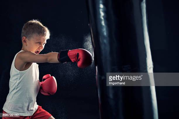 Little boy training boxing with punching bag