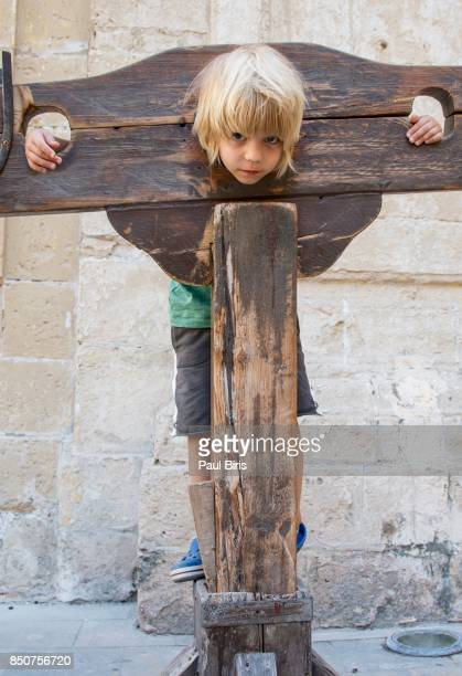 Little  boy trapped in a  Wooden Pillory, Mdina, Malta