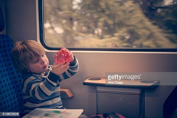 Little boy  (3) travelling in a train looks his piggy bank.