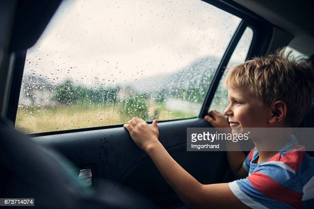 Little boy travelling in car on a rainy day