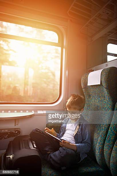 Little boy travelling on train and playing with tablet