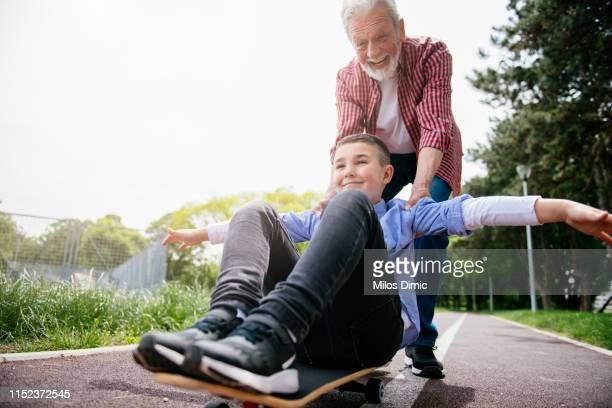 little boy trying skateboard - caneleira roupa desportiva de proteção imagens e fotografias de stock