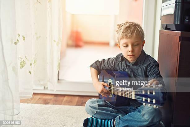 Little boy tuning his little blue acoustic guitar.