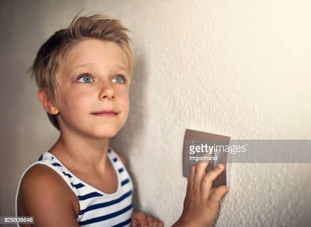 Little boy turning on light
