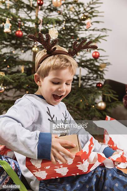little boy unwrapping a christmas gift - gift lounge stock-fotos und bilder
