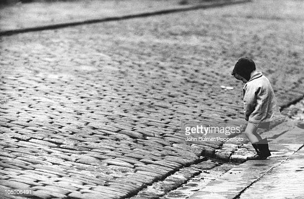 A little boy urinates in the street in Nelson Lancashire circa 1960