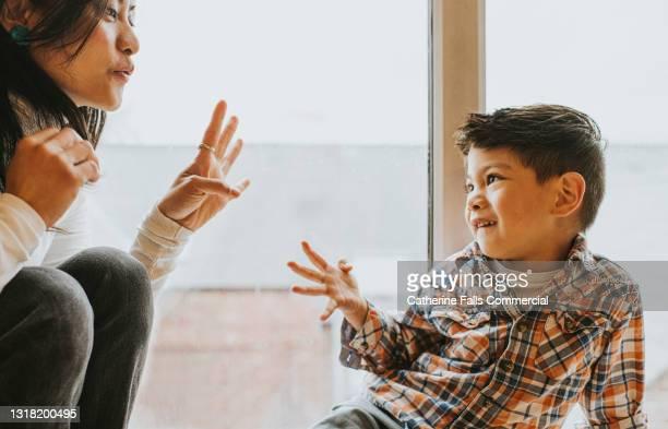 a little boy uses sign language to talk to a woman - vier gegenstände stock-fotos und bilder