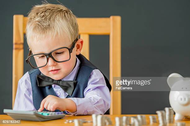 little boy using a calculator - calculator stock photos and pictures
