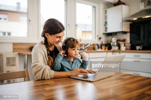kleiner junge mit einem laptop mit seiner mutter die küche - istock stock-fotos und bilder