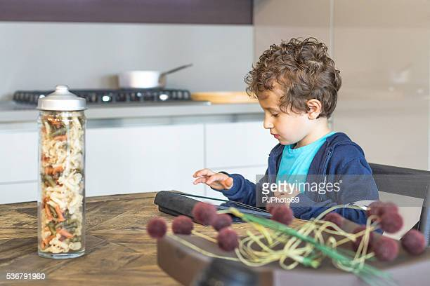 little boy using digital tablet at home kitchen - pjphoto69 stock pictures, royalty-free photos & images