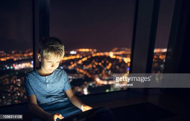 little boy using digital tablet at night - imgorthand stock photos and pictures