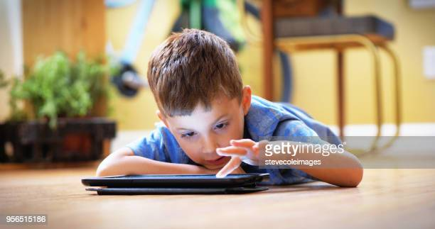 Little boy using digital tablet laying down on floor inside home.