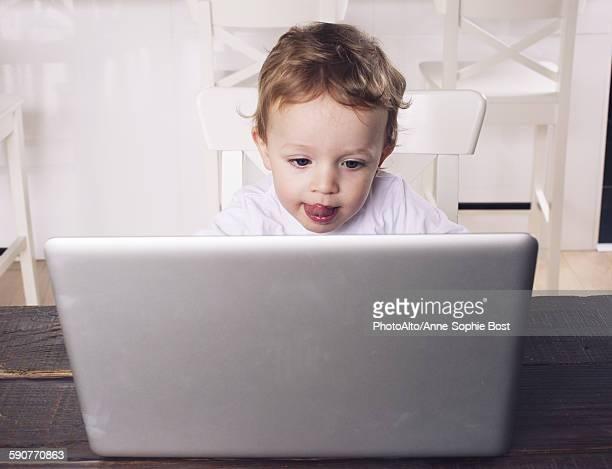 little boy using laptop computer - commodité photos et images de collection